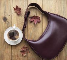 Bolso de cuero, taza de café y hojas de otoño sobre un fondo de madera foto