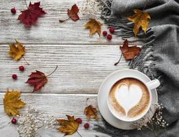 Cup of coffee and dry leaves on white wooden background photo