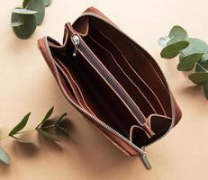 Monedero de cuero marrón recostada sobre un fondo marrón claro foto