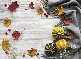 Autumn maple leaves, pumpkins and woolen scarf on a wooden background. photo
