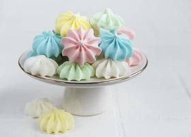 Small colorful meringues on the ceramic  stand photo