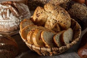 Set of wheat and rye bread with a spoon of salt on a wooden background photo