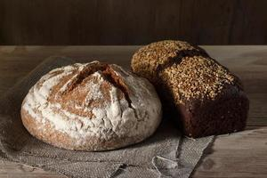 Round and black square bread loaf and wooden background photo