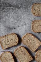 Sliced grain  whole wheat bread on dark rustic wooden background photo