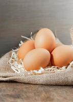huevos orgánicos frescos en arpillera con pasto seco en la mesa de madera. foto