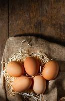 Fresh Organic eggs in burlap with dry grass on wood table. photo