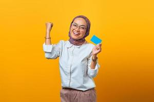 Cheerful Asian woman celebrating luck and holding blank card photo