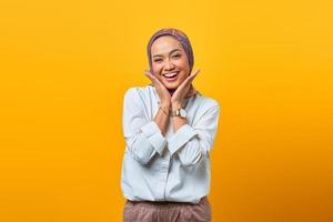 Portrait of cheerful Asian woman hand touch face photo