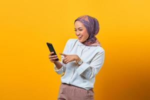 Cheerful Asian woman looking at smartphone getting good news photo