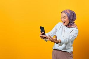 Excited Asian woman looking at smartphone getting good news photo
