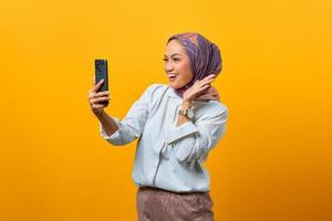 Cheerful Asian woman looking at smartphone with raised hand photo