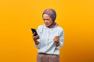 Angry Asian woman looking at smartphone getting bad news photo