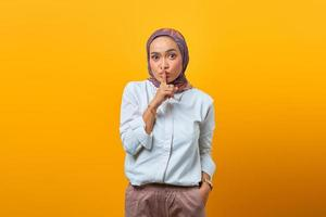 Beautiful Asian woman making finger on lips mouth silent quiet gesture photo