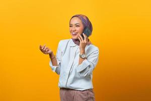 Cheerful Asian woman talking with her friend by cell phone photo