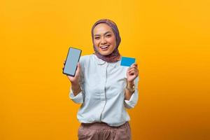 Cheerful Asian woman holding smartphone and blank card photo