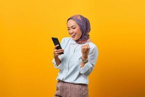 Emocionada mujer asiática sosteniendo teléfono móvil celebrando la suerte foto