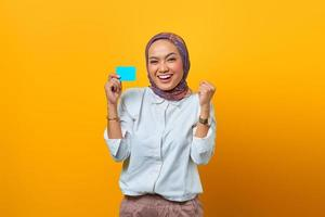 Excited Asian woman holding blank cards with victory expression photo