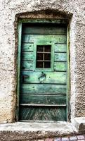 Green wooden door with weather-damaged window in San Martino di Castrozza, Trento, Italy photo