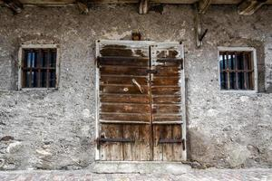 Old weather-damaged wooden door in San Martino di Castrozza, Trento, Italy photo