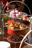 macarrones, pasteles de cesta y chocolates sobre un soporte especial foto