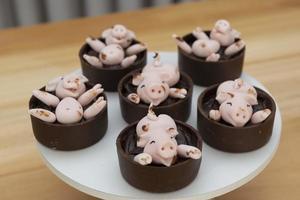caramelos decorados, lindos cerdos rosados felices jugando en el barro foto