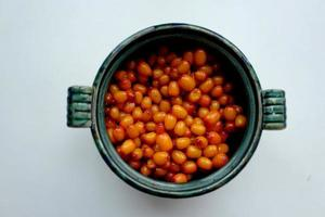 Sea buckthorn berries in a green round cup photo