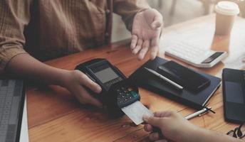 primer plano, de, asiático, cliente, utilizar, el suyo, tarjeta de crédito, para, deslizar, con, edc foto