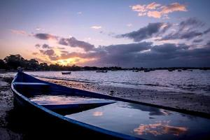 blue boat on the sunset, reflection of the clouds on the water photo