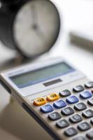 Selective focus on plus tax button of calculator with blurry clock. photo