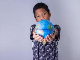boy holding a globe stand out in front . photo