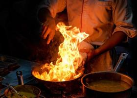 Chef cooking with flame in a frying pan on a kitchen stove photo