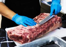 chef cuts raw meat with a knife on a board, Cook cuts raw meat photo