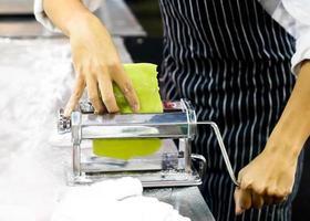 Chef making dough for pastry, fresh pasta and pasta machine on kitchen photo