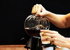 Barista making coffee, Barista pouring drip coffee into glass photo