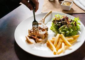 Pork chop steak with salad and french fries photo