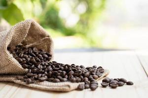 Los granos de café salen del saco en el piso de madera por la mañana. foto