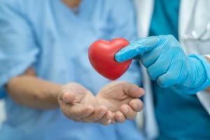 El doctor le da un corazón rojo al paciente asiático de la mujer mayor foto
