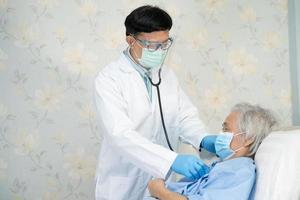 médico asiático ayuda a paciente anciana asiática en el hospital de enfermería. foto