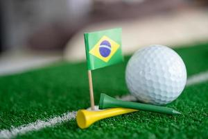 Golf ball with Brazil flag and tee on green lawn photo