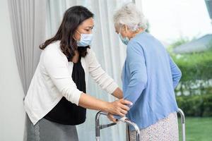 Help Asian senior woman patient walk with walker in hospital. photo