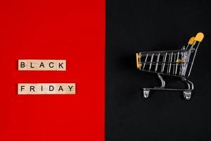 concepto de venta de viernes negro. Mini carrito de compras sobre fondo rojo. foto