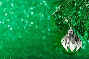 Silver Christmas ball on shiny green background. New Year concept photo