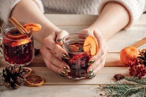 Woman holds cup of hot mulled wine in her hands. photo