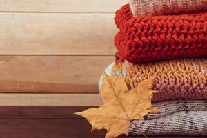 pila de suéteres de punto calientes. jerséis de lana y hoja de arce foto