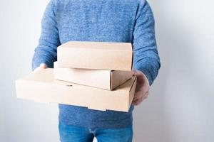 Anonymous young man with jeans delivering some cardboard boxes photo