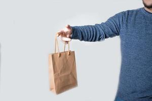 Young anonymous man holding a paper bag photo
