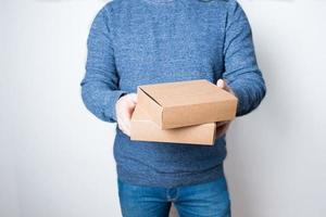 Anonymous young man with jeans delivering two boxes photo
