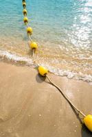 Floating buoy and rope dividing the area on the beach photo
