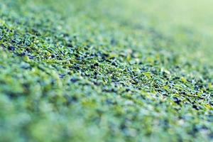 Plastic artificial grass and the rubber pellets on school yard photo