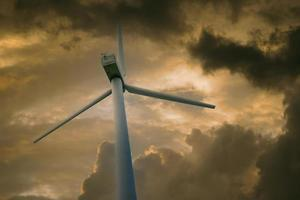 Wind power plant against a sky with white clouds photo